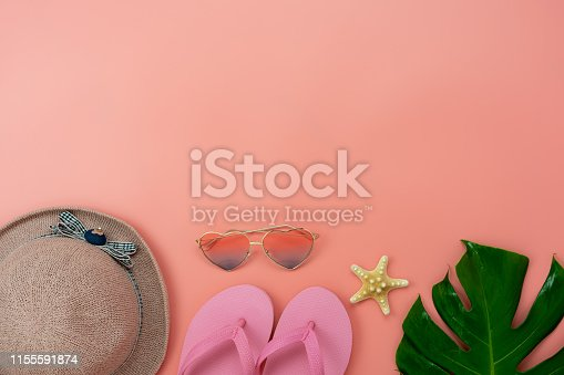 Table top view accessory of clothing women plan to travel in summer holiday background concept.monstera leaves with essential items sunglasses & slippers on modern rustic pink paper.Space for design.
