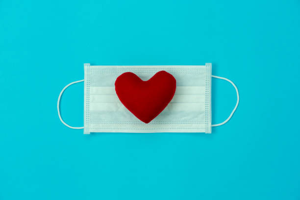 Table top view aerial image of accessories healthcare & medical background concept.Essential equipment tools mask on red love heart on blue paper.Flat lay essential items for protect viral Covid-19. stock photo