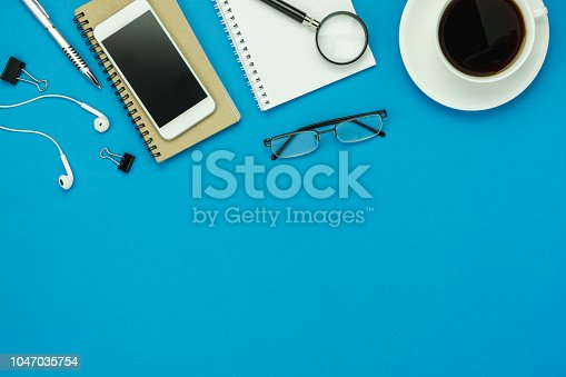 istock Table top view aerial image of accessories office desk background concept.Flat lay of variety object the mobile phone & pen and coffee with earphone on modern rustic blue paper with copy space. 1047035754