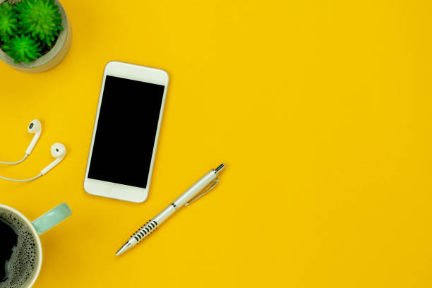 Table top view aerial image of accessories office desk background concept.Flat lay of variety object the white white mobile phone & tree pot and with earphone on modern rustic yellow paper and space. stock photo