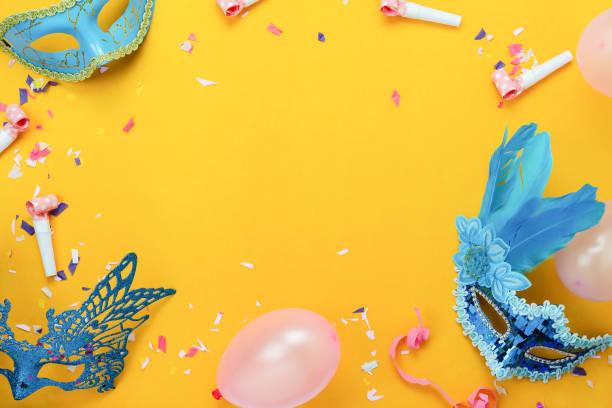 imagen aérea de la vista superior de tabla de fondo festival carnaval colorido hermoso. plano pone objeto accesorio el confeti de la máscara y la decoración y el globo en papel amarillo moderno en el estudio de escritorio de oficina en casa. - carnaval fotografías e imágenes de stock