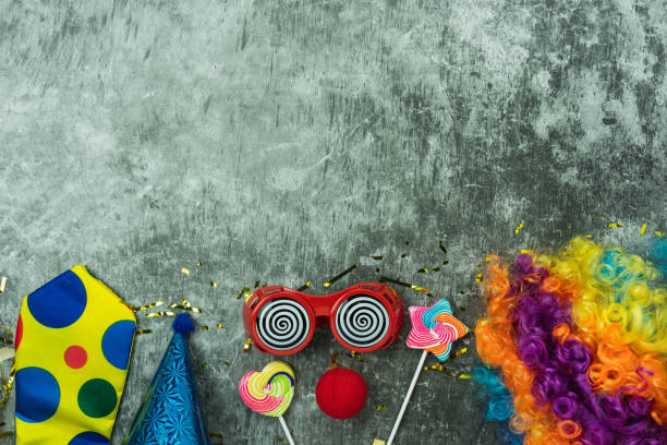 Table top view aerial image of beautiful colorful carnival festival background.Flat lay accessory object the several mask & decor confetti on modern grey cement at home office desk studio.copy space. stock photo
