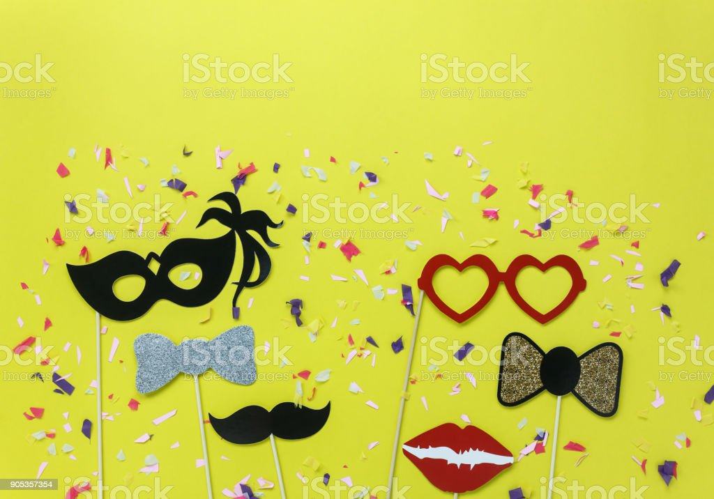 Table top view aerial image of beautiful colorful carnival mask or photo booth props background.Flat lay objects on modern rustic yellow wallpaper at office desk studio.space for creative mock up. stock photo