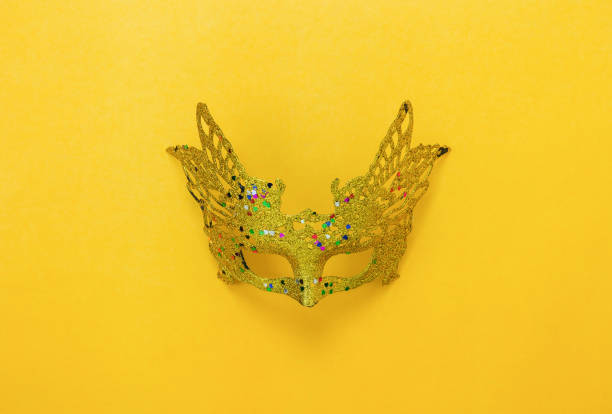 Table top view aerial image of beautiful colorful carnival season or photo booth prop Mardi Gras background.Flat lay object gold mask on modern yellow wallpaper.Free space for creative design mock stock photo