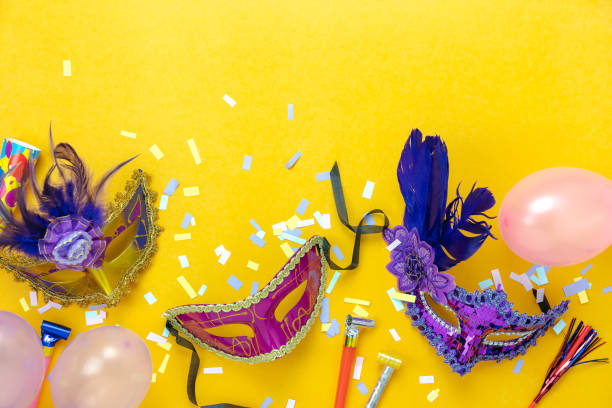 Table top view aerial image of beautiful colorful carnival season or photo booth prop Mardi Gras background.Flat lay variety mask with decorations and confetti & pink balloon on yellow wallpaper. stock photo