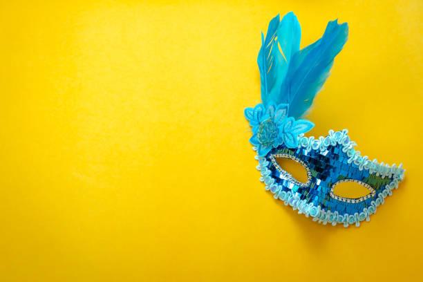 imagem aérea da vista superior tabela de belo colorido carnaval temporada ou foto cabine prop fundo de mardi gras. objeto plano leigo fechar máscara azul no papel de parede amarelo moderno. espaço livre para a simulação acima do texto. - carnaval - fotografias e filmes do acervo