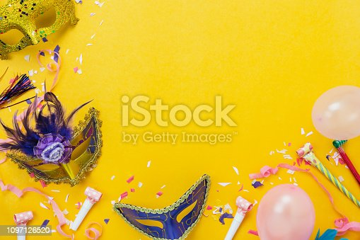 Table top view aerial image of beautiful colorful decorations carnival festival background.Flat lay accessory object the mask & decor confetti and pink balloon on modern yellow paper.copy space.