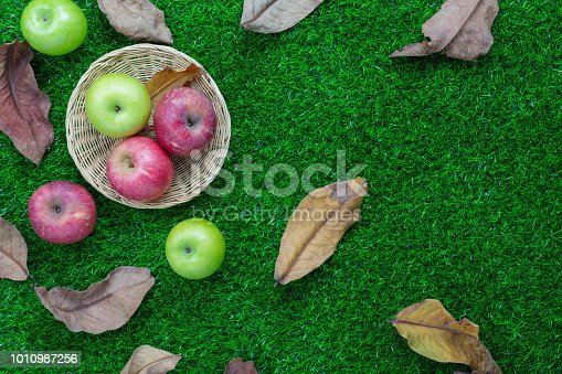 istock Table top view aerial image of decoration Fall harvest or Rosh Hashanah day background concept.Flat lay apple in basket with dry leaf all objects on modern rustic green grass.Copy space for add text. 1010987256