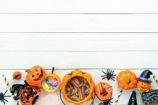 Table top view aerial image of decoration Happy Halloween day background concept.Flat lay accessories essential object to party the pumpkin & sweet candy on black wooden.Space for creative design.