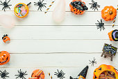 istock Table top view aerial image of decoration Happy Halloween day background concept.Flat lay accessories essential object to party the pumpkin & balloon on white wooden.Space for creative design text. 1047035800