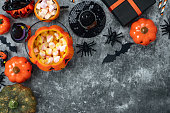 istock Table top view aerial image of decoration Happy Halloween day background concept.Flat lay accessories essential object to party the pumpkin & sweet candy on rustic stone.Space for creative design. 1179502410
