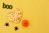 istock Table top view aerial image of decoration Happy Halloween day background concept.Flat lay accessories essential object to party the pumpkin & sweet candy on yellow paper.Space for creative design. 1179502433