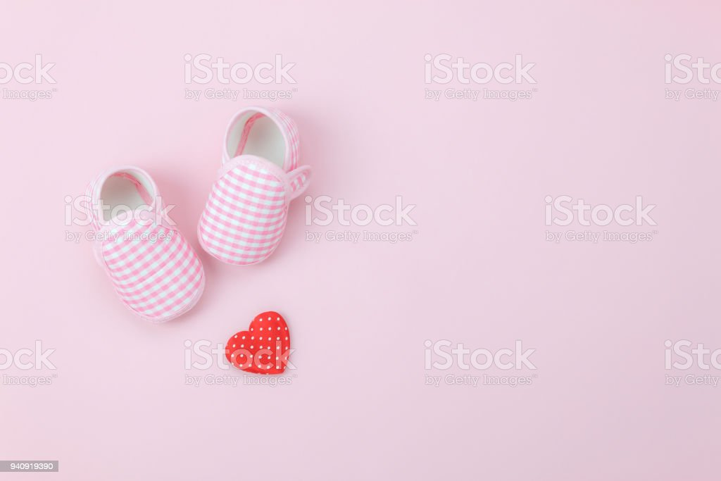 Table top view aerial image of decoration Happy mother's day holiday background concept.Flat lay red heart & baby shoes on modern beautiful pink paper at home office desk.Design pastel tone and space. stock photo