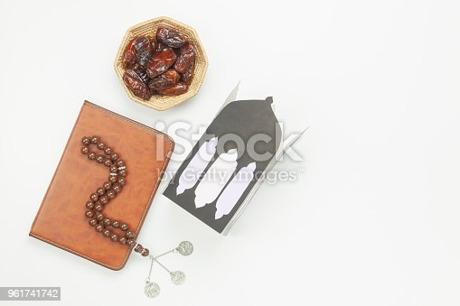 istock Table top view aerial image of decoration Ramadan Kareem holiday background.Flat lay date in wood basket with rosary & DIY paper lantern.The holy book of Koran on modern rustic white wooden.copy space 961741742
