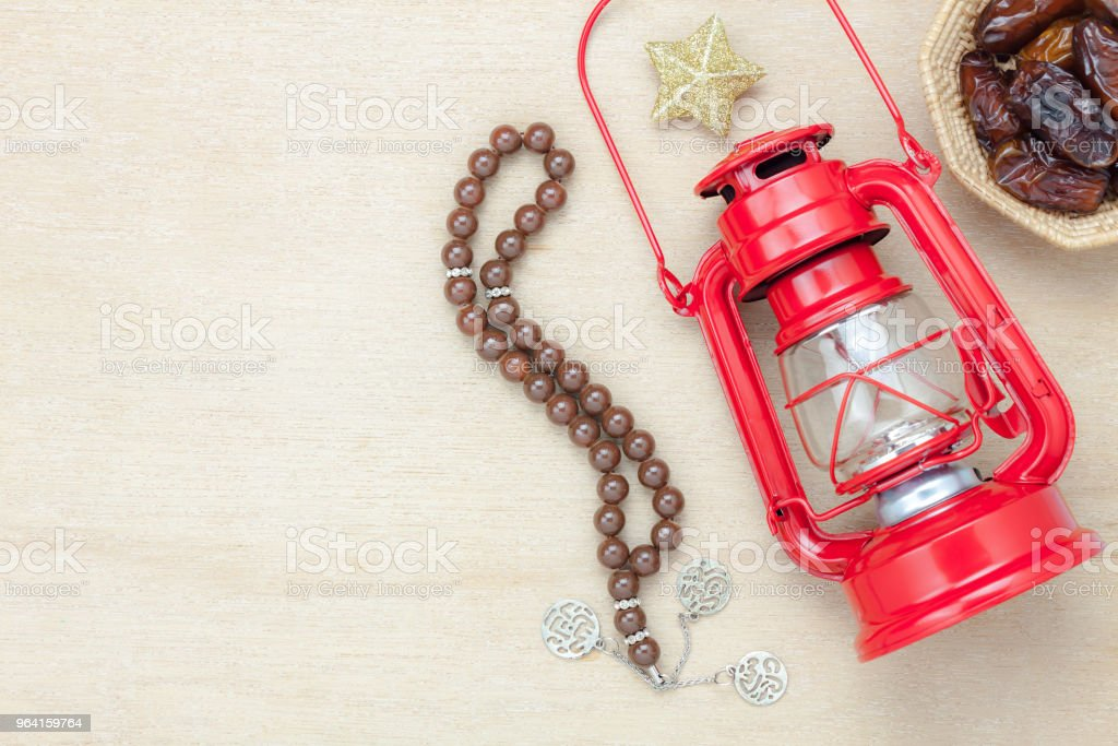 Table top view aerial image of decoration Ramadan Kareem holiday background.Flat lay date in wood basket with brown rosary & red lantern.Halal meal set for fasting is obligatory for Muslim on wooden. stock photo
