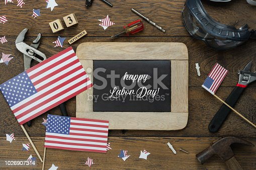 istock Table top view aerial image of decoration the sign of USA labor day on Sep 3,2018 background concept.Flat lay accessories US flag and essential tools worker on brown wooden.Text season on blackboard. 1026907314