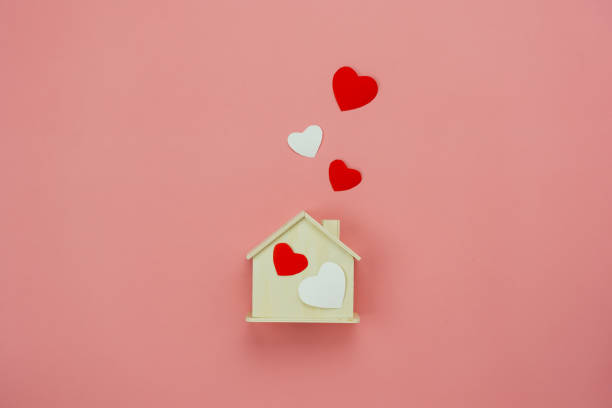 Table top view aerial image of decoration valentine's day background concept.Flat lay essential items colorful pastel love shape with wooden house on modern rustic pink paper.Mock up creative design. stock photo