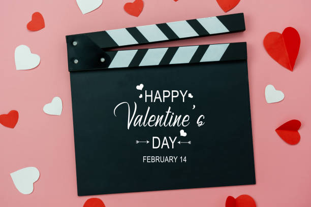 Table top view aerial image of decoration valentine's day background concept.Flat lay essential items colorful love shape paper cut with welcome word on movie clapper with modern pink wallpaper. stock photo