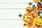 istock Table top view aerial image of decorations Happy Halloween day background holiday concept.Flat lay objects to party pumpkins and spider with candy sweet on white wooden wallpaper.Copy space for text. 1178690804
