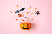 istock Table top view aerial image of decorations Happy Halloween day background holiday concept.Flat lay objects to party Jack O lantern pumpkins bucket and spider with candy sweet on pink  paper. 1179502333