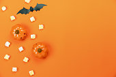 istock Table top view aerial image of decorations Happy Halloween day background holiday concept.Flat lay objects to party pumpkins and bat with candy sweet on orange  paper.Copy space for creative  text. 1179502343