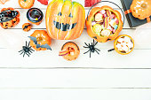 istock Table top view aerial image of decorations Happy Halloween day background holiday concept.Flat lay objects to party pumpkins and spider with candy sweet on white wooden wallpaper.Copy space for text. 1179502355