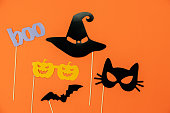 istock Table top view aerial image of decorations Happy Halloween day background holiday concept.Flat lay objects to party pumpkins photo booth prop and spider & bat hat witch on orange  paper wallpaper. 1179502363