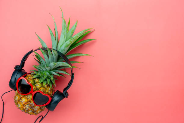 table top view aerial image of food for summer holiday season & music background concept.flat lay object the pineapple listening radio by black headphone for sign of seasonal on modern pink paper. - политическая партия стоковые фото и изображения