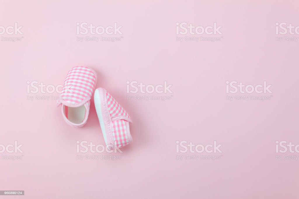 Table top view aerial image of kid fashion background concept.Flat lay shoe baby on modern beautiful rustic pink paper at office desk.Free space for creative design text and wording.Pastel tone stock photo