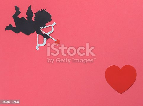 istock Table top view  aerial image of sign of valentines 's day background concept.DIY photo booth props the cupid shoot arrow to red heart on modern rustic pink wallpaper at home office desk studio. 898516490