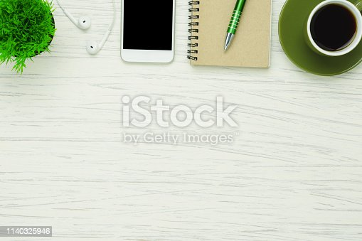 istock Table top view aerial image stationary on office desk background concept.Flat lay objects the black coffee with essential accessory & mobile phone.Items on modern white wooden at home studio. 1140325946
