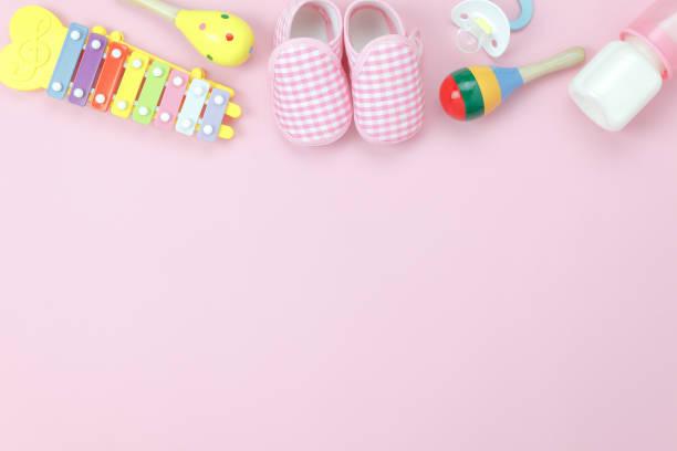 tabelle draufsicht dekoration kinderspielzeug für hintergrund-konzept entwickeln. flache laien babyschuhe mit artikel kind auf modernen rosa papier am schreibtisch. textfreiraum für text hinzufügen. kreative geruhen pastell ton tapete. - sommerfest kindergarten stock-fotos und bilder
