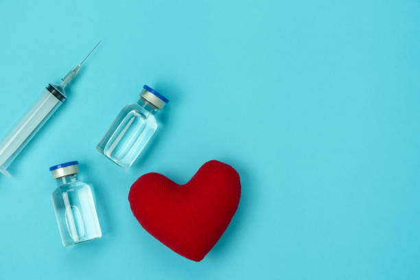 Table top view  image of accessories healthcare & medical with coronavirus background concept.vaccine bottle with heart shape and Syringe on blue paper.Flat lay items for doctor using treat patient. stock photo
