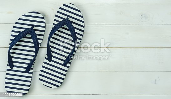 955947208 istock photo Table top view of accessory for travel on summer holiday background concept.Flat lay of blue slippers on modern rustic white wooden.copy space for creative design text & word mock up. 1221950596