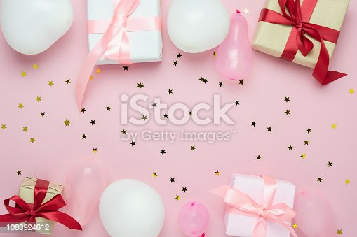 950793576 istock photo Table top view of birthday decorations & Happy new year ornaments concept.Flat lay essential objects the balloon & gift box on modern rustic pink paper background at home studio office desk. 1083924612