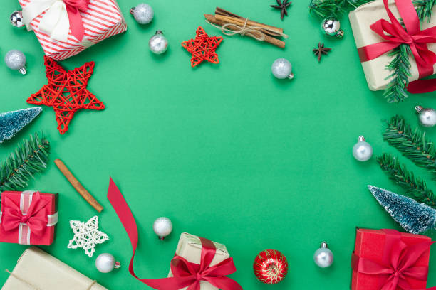 Table top view of Merry Christmas decorations & Happy new year ornaments concept.Flat lay essential objects the fir tree & gift box on modern rustic green paper background at home studio office desk. stock photo