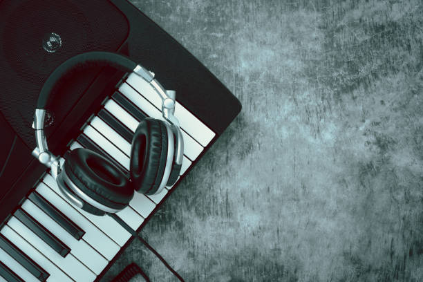 Table top view of music instrument tools concept background.Flat lay of sign to sing for musician or party equipment.Headphone and electric piano on modern grey cement.space for creative design. stock photo