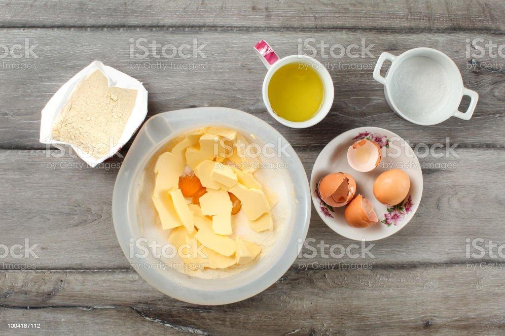 Vista superior de tabela em ingredientes para a preparação do bolo. Saco de farinha, tigela com manteiga e gema de ovos, Copa com glair, cascas de ovos e açúcar, colocado na mesa de madeira cinza. - foto de acervo
