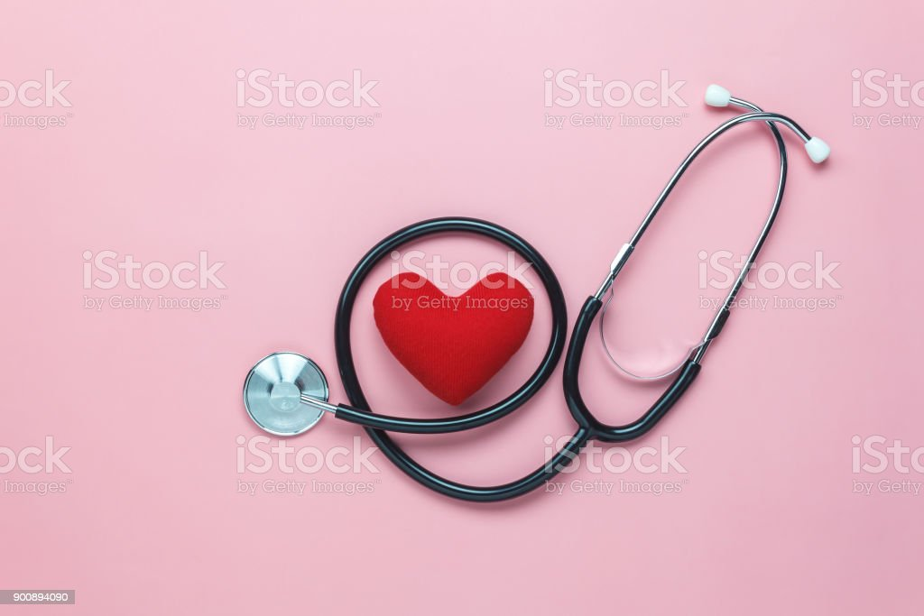 Table top view shot of arrangement equipment medical background concept.Red heart & stethoscope on modern rustic pink paper.An idea essential accessories for doctor for  care patient  in hospital. stock photo