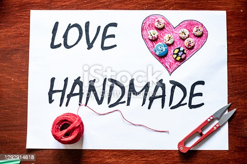 istock Table top view with sewing equipment and inscription love handmade 1292914618