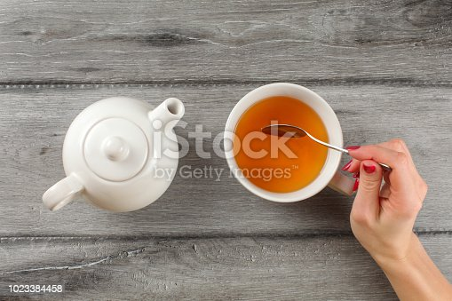 Table top view - woman hand holding spoon, stirring tea in white porcelain cup.