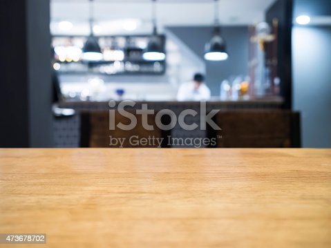 886308526 istock photo Table top with Blurred kitchen and chef on background 473678702