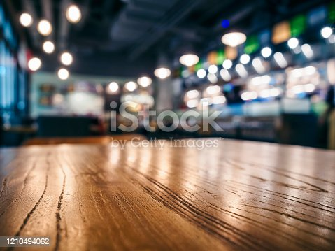 877010878 istock photo Table top wooden counter Bar cafe restaurant  Blur background 1210494062