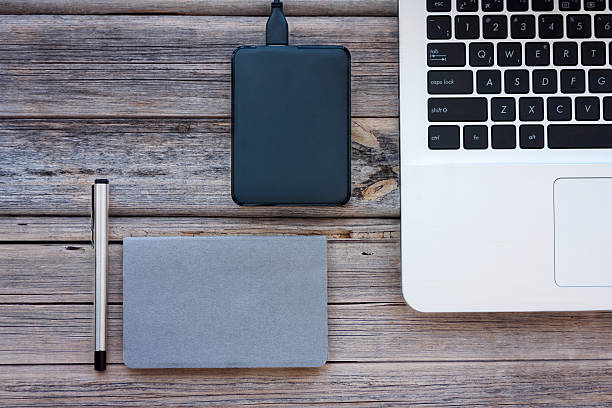table view of office supplies - external hard disk drive stock photos and pictures