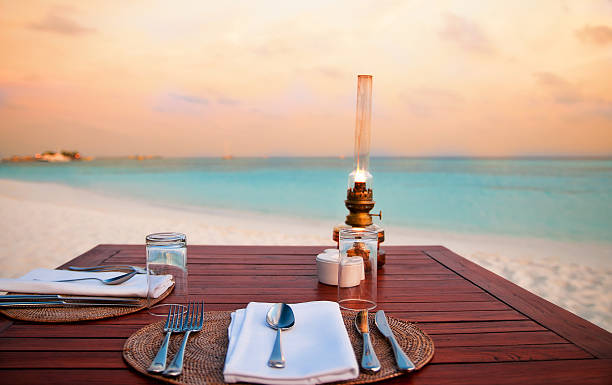 A table with a candlelight dinner at the beach at dawn stock photo