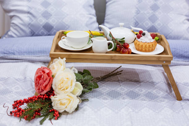 table with a Cup and a flower on the bed, coffee in bed in the morning stock photo