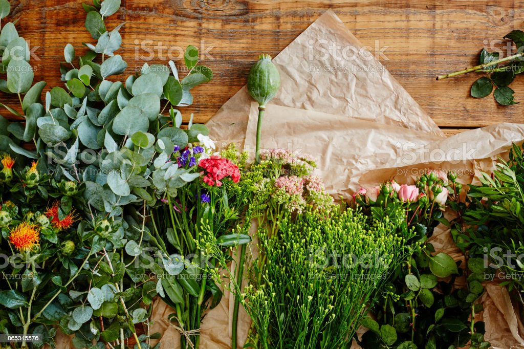table with a wild mix of flowers flowershop behind the scenes stock photo