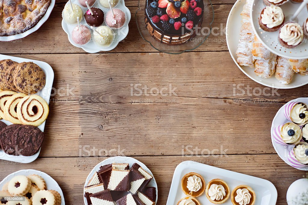 Table with cake, pie, cupcakes, tarts and cakepops. Copy space. stock photo