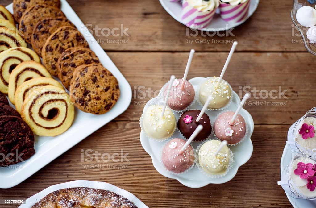 Table with cakepops, cookies and cupcakes. Wooden background. stock photo