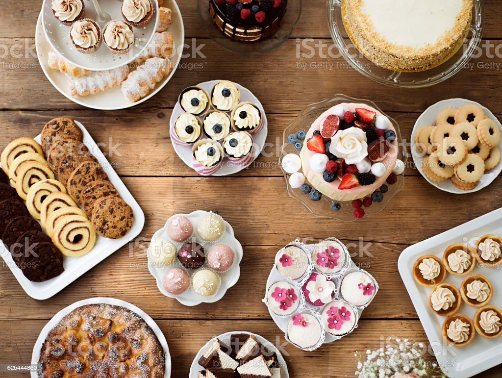 Table with cakes, cookies, cupcakes, tarts and cakepops. stock photo
